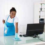 Happy Young African Female Janitor Cleaning Desk With Rag In Office